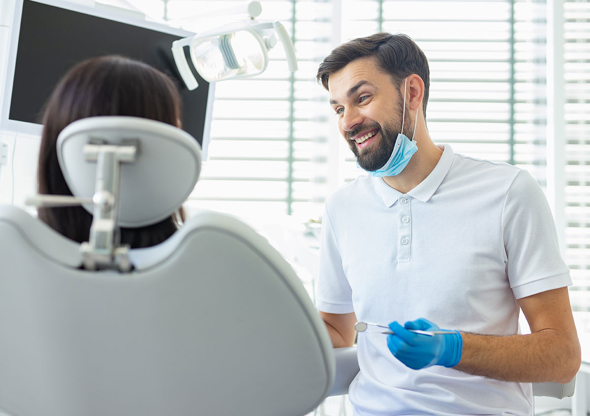 Dentist smiling and talking to patient